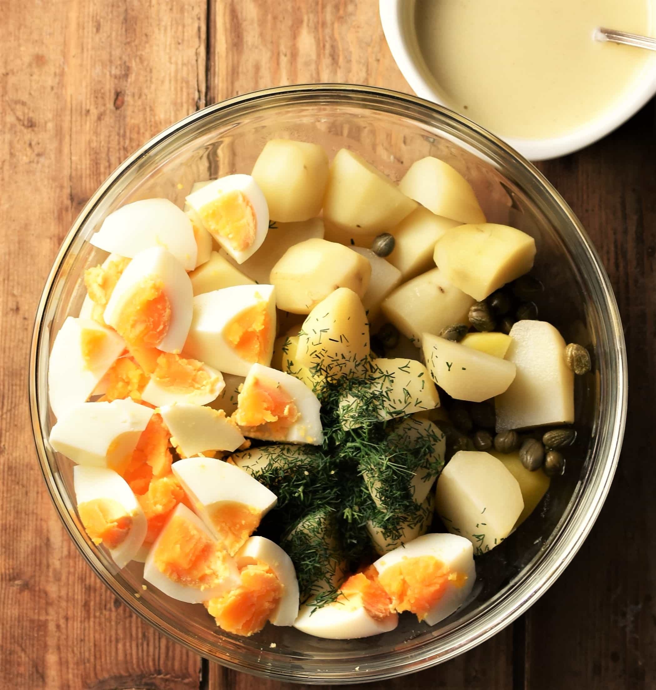 Cubed peeled potatoes and hard boiled egg, capers and dill in bowl with creamy dressing in top right.