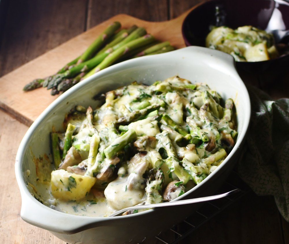 Side view of asparagus mushroom casserole with potatoes and spoon in oval dish, with asparagus tips in background.