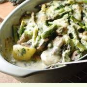 Side view of asparagus, mushroom and potato bake with creamy sauce and spoon in green oval dish, with asparagus tips in background.