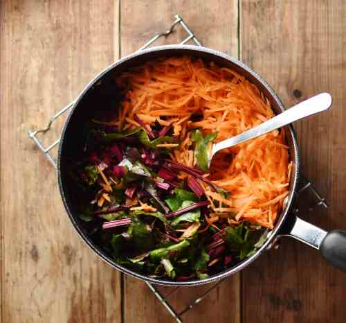 Grated carrot and chopped beet leaves with spoon inside large pot.