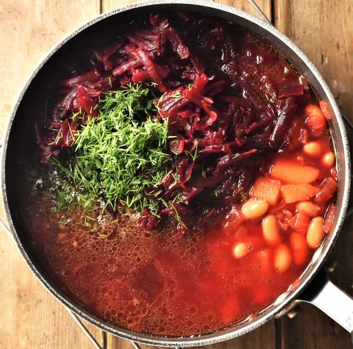 Borscht in pot with grated beets, beans and chopped dill.