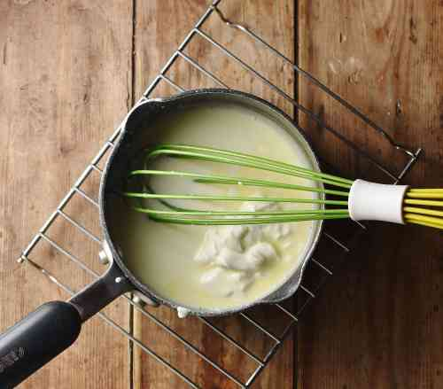 White sauce with yogurt and green whisk in saucepan.