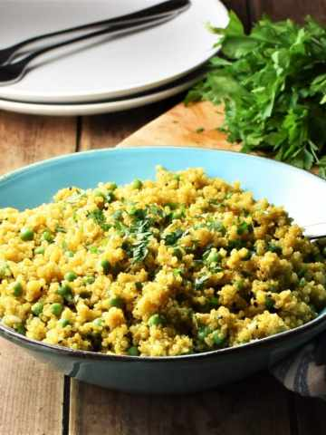 Close-up view of curried quinoa with peas in blue bowl with spoon, 2 white plates with forks and fresh herbs in background.