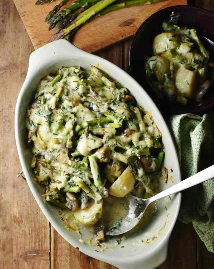 Asparagus, potatoes and mushrooms in creamy sauce with spoon in green oval dish, with green cloth to the right, potato mixture in dish and asparagus tips in background.
