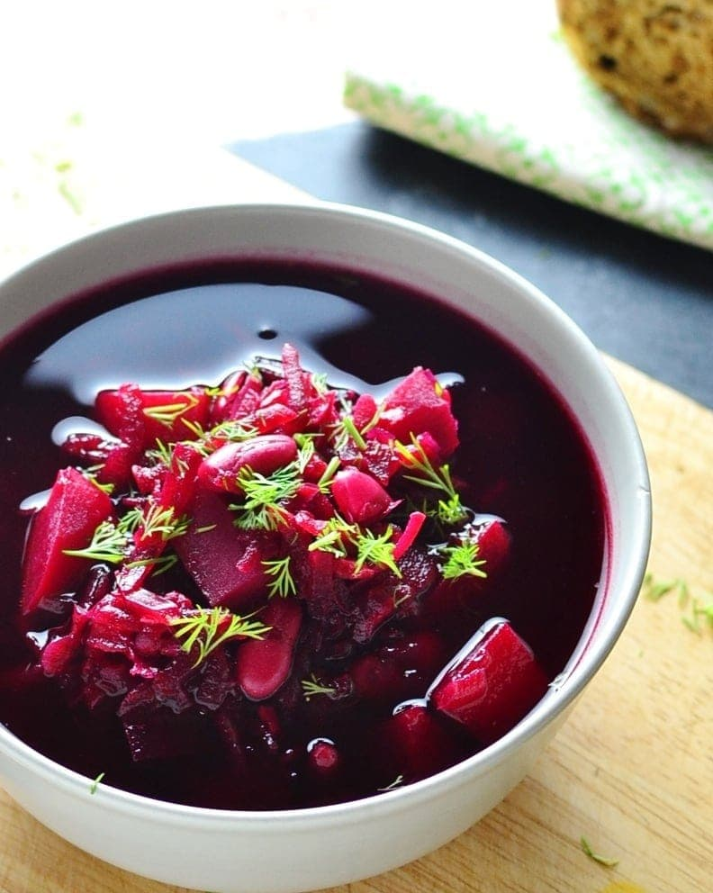 Beet soup with beans, cubed potato and dill in white bowl on wooden board.