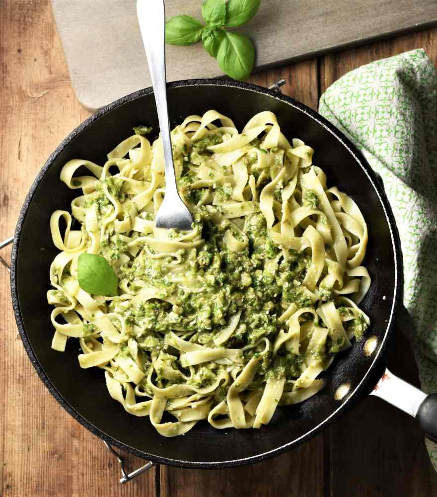 Top down view of tagliatelle pasta with asparagus pesto in skillet with fork, green cloth and basil in background.