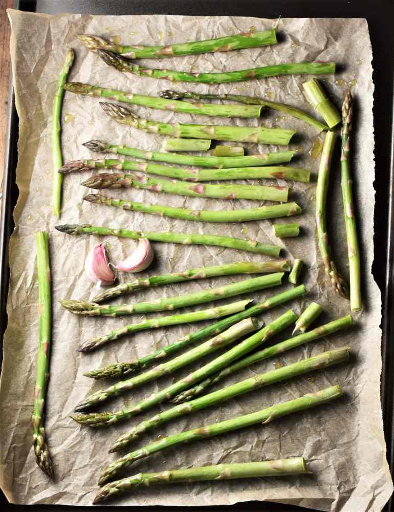 Asparagus tips and 2 garlic cloves on top of baking sheet lined with parchment.
