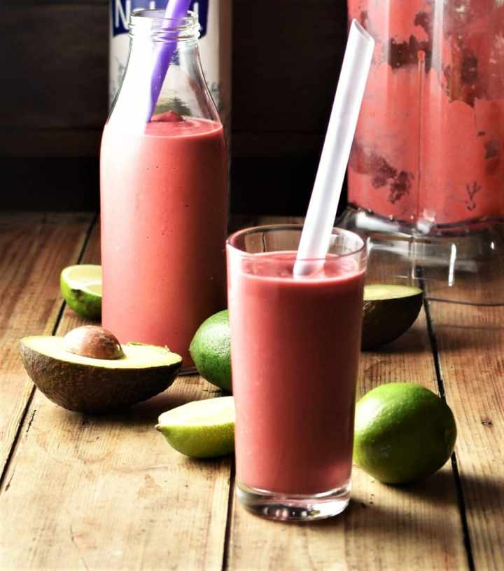 Side view of raspberry avocado smoothie in glass with straw with avocado, limes, smoothie in bottle and blender in background.