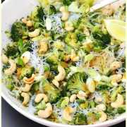 Close-up view of bean thread noodles salad with broccoli and cashews in white bowl.