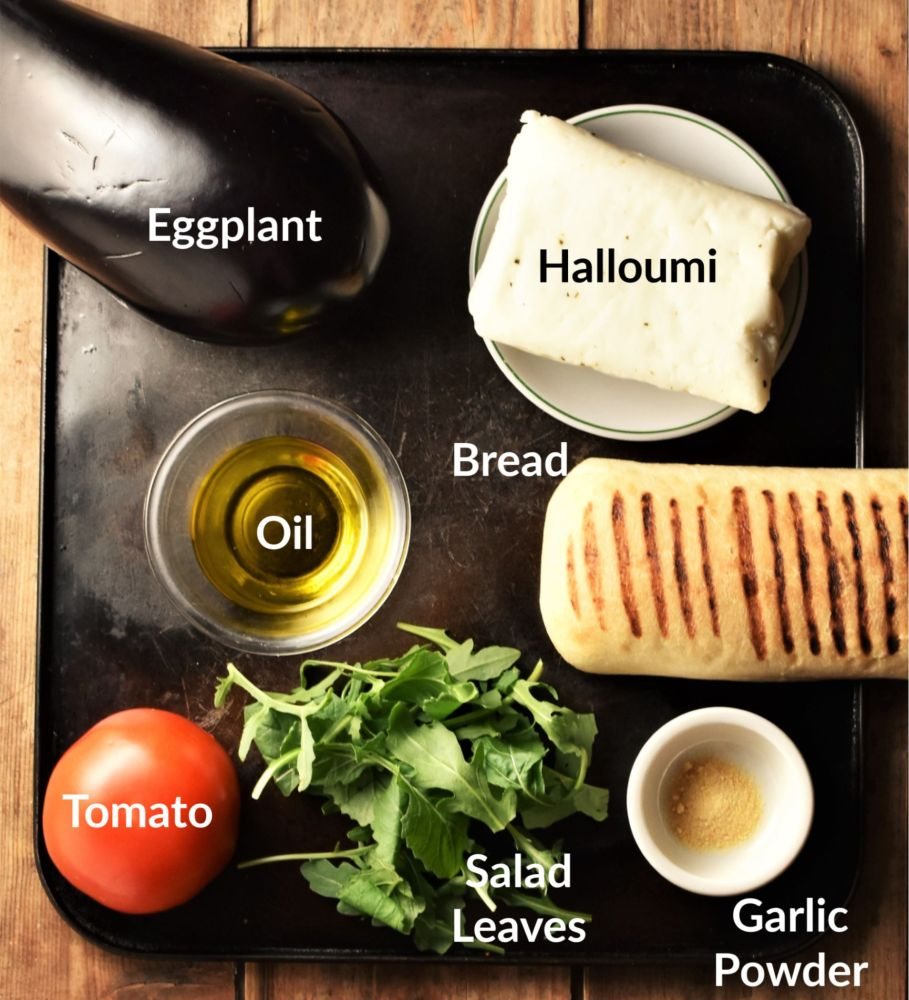 Eggplant sandwich ingredients on top of black tray.