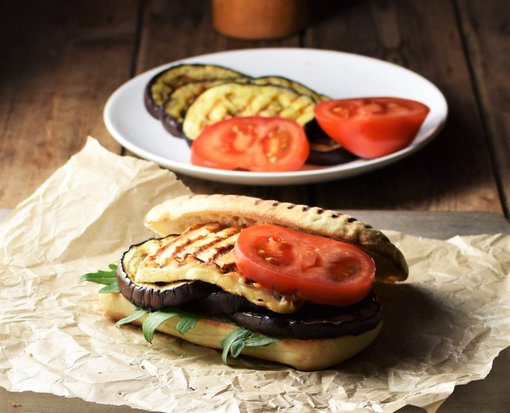 Side view of open eggplant halloumi tomato sandwich on top of paper, with grilled eggplant slices and tomato in background.