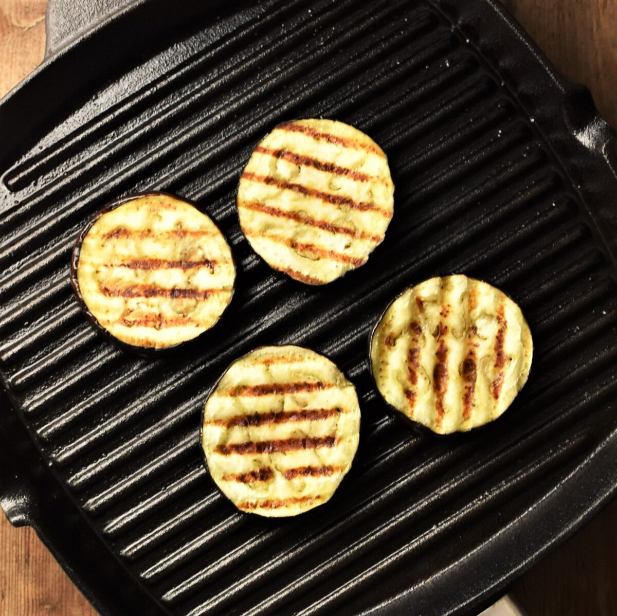 4 grilled eggplant slices in griddle pan.