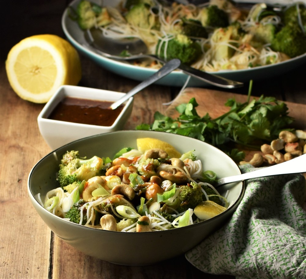 Side view of broccoli noodle salad in green bowl with spoon, dressing and herbs in background.