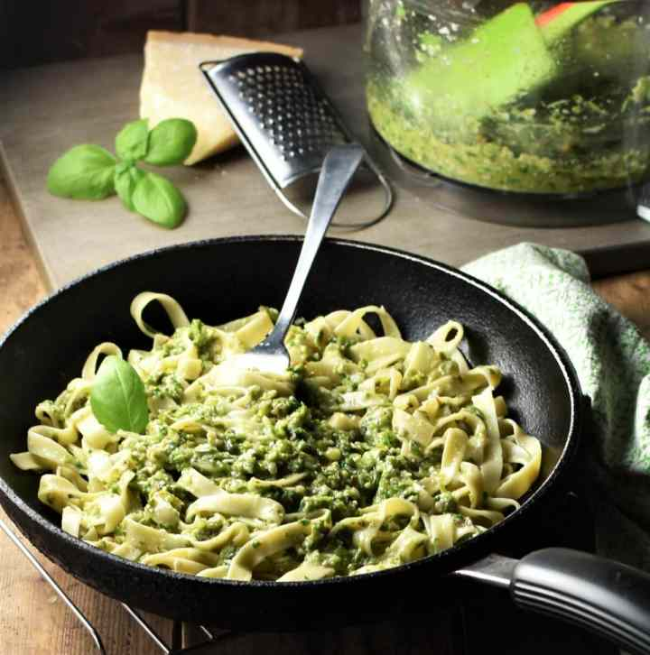 Side view of tagliatelle pasta with asparagus pesto and fork in skillet, with pesto, cheese and basil in background.
