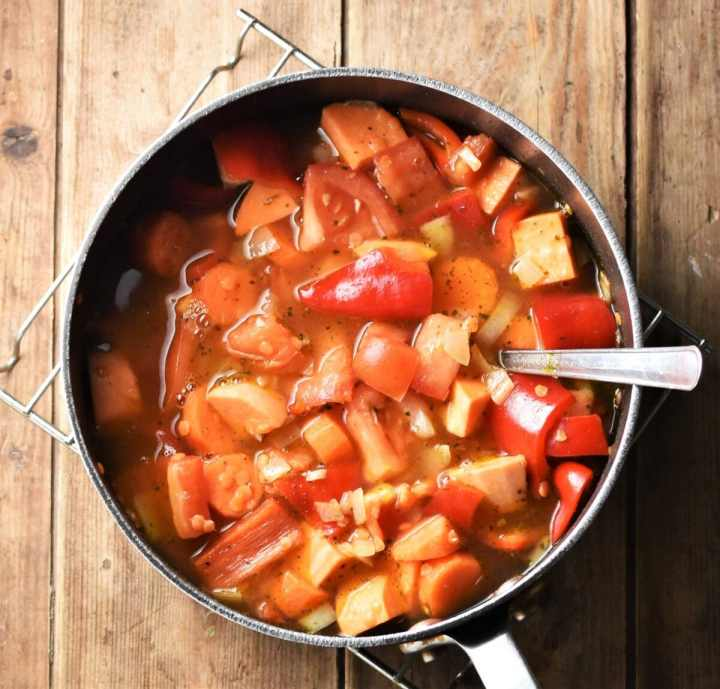 Chopped sweet potato, red pepper and carrot with stock in large pot with spoon.
