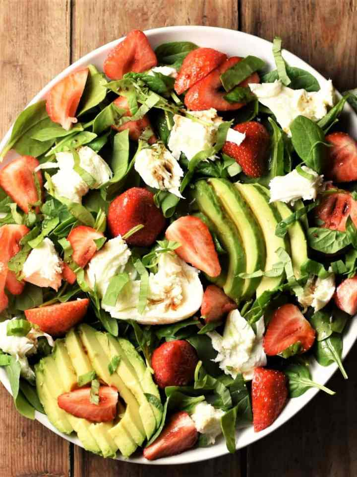 Top down view of strawberry and spinach salad with avocado and mozzarella on white plate.