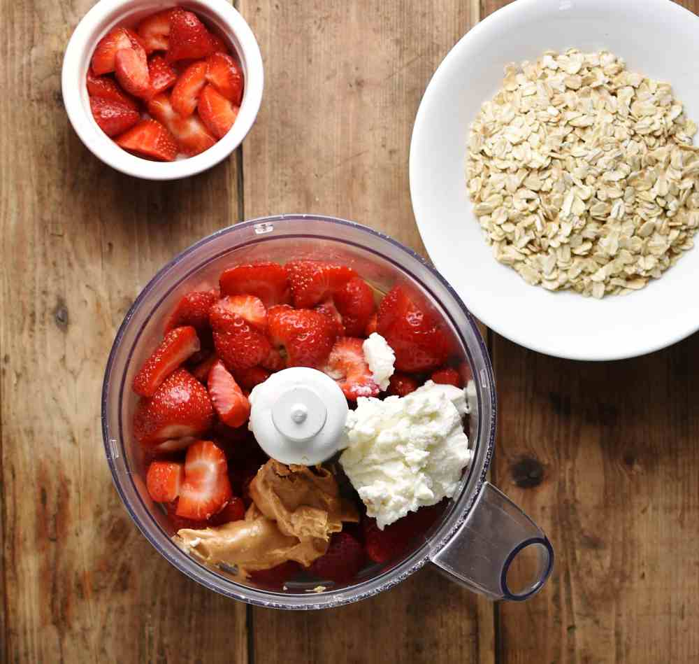 Top down view of chopped strawberries, peanut butter and ricotta in blender, with oats in white bowl and chopped strawberries in white dish.
