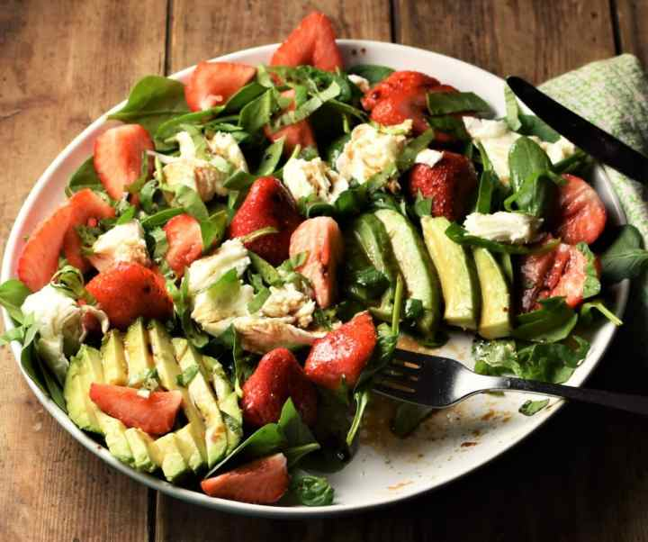 Avocado, strawberries, spinach and strawberry salad on white plate with fork.