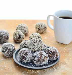 Chocolate energy balls on black plate with white coffee cup on wooden table.