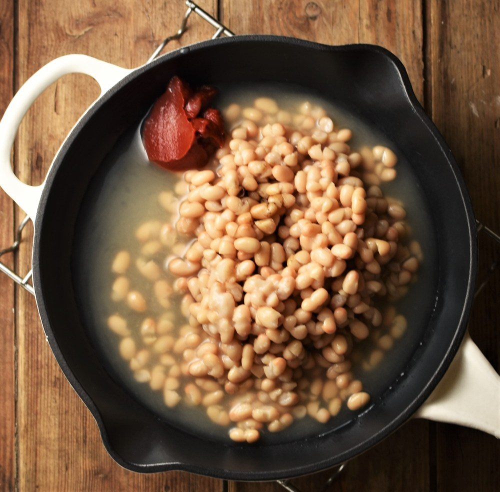 Beans with tomato paste in skillet.
