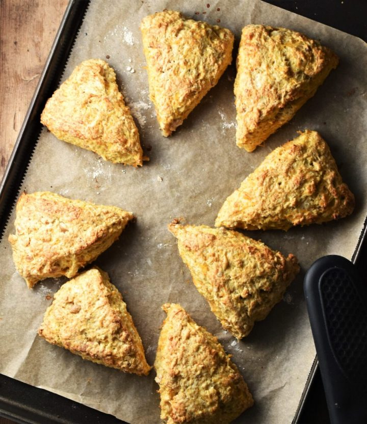 8 baked scones on top of baking sheet lined with parchment paper.