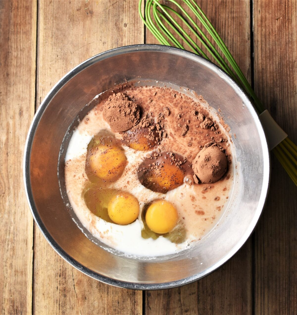5 eggs, milk and cocoa powder in large metal bowl with green whisk to the right.