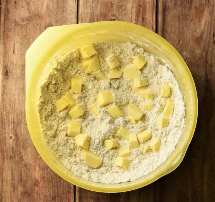 Flour mixture and cubed butter in large yellow bowl.
