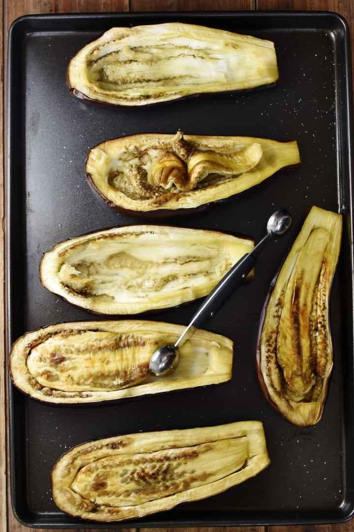 6 roasted eggplant halves with melon baller.