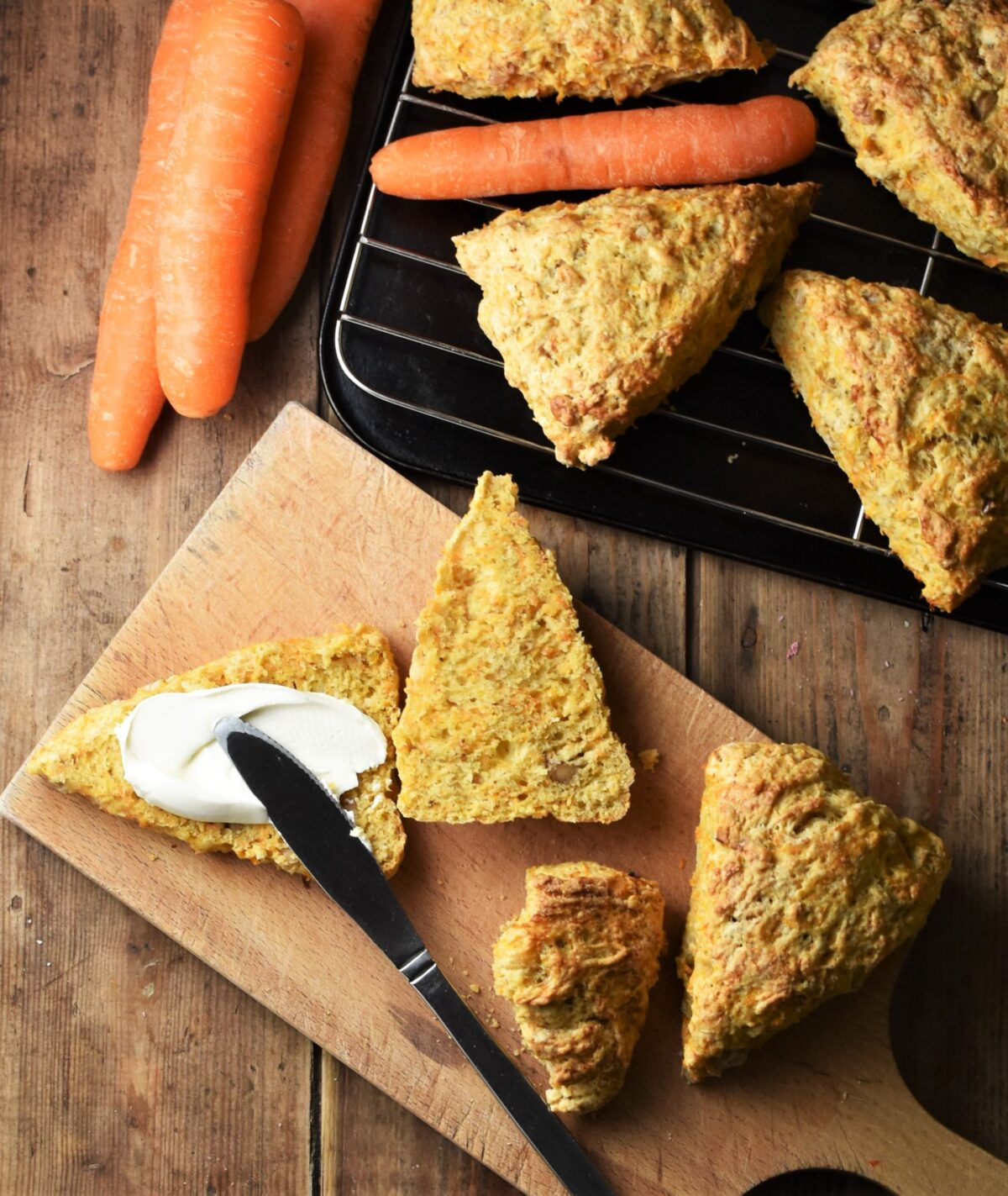 Carrot scones on top of wooden board, 1 with cream cheese and knife on top, and scones with raw carrots on top of black tray.