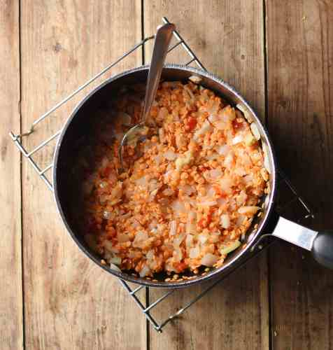 Fried onions and red lentils in large pot with spoon on top of cooling rack.