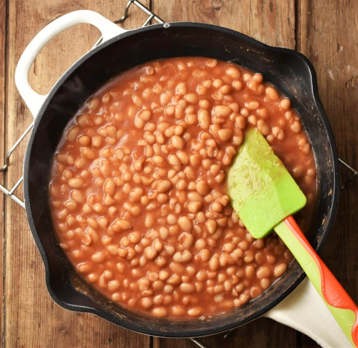 Top down view of beans in tomato sauce in skillet with green spatula.