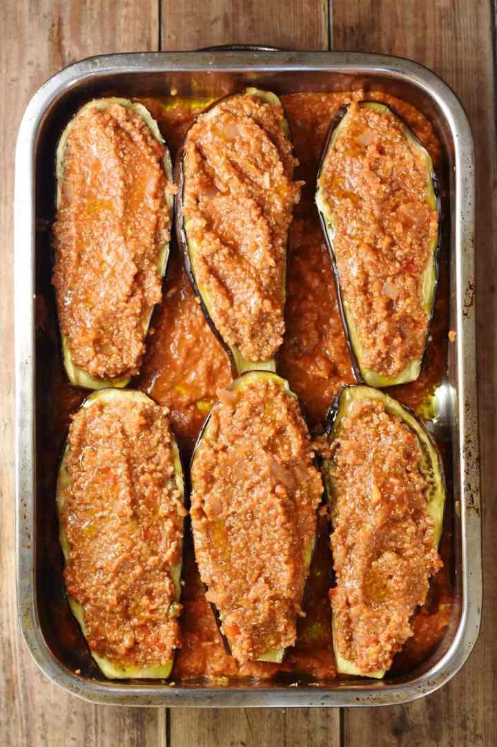 6 quinoa stuffed eggplant halves in tomato sauce in large rectangle oven dish.