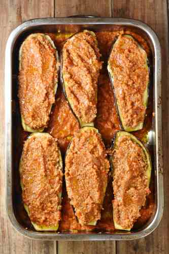 6 quinoa stuffed eggplant halves in tomato sauce in large rectangle oven dish.