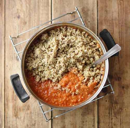 Tomato sauce and quinoa with spoon in saucepan.