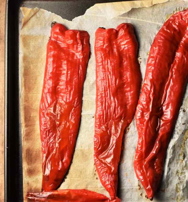 Top down view of 3 halved roasted pointed red peppers on top of baking sheet with parchment.