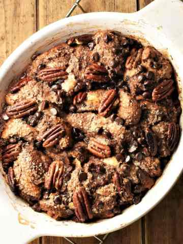 Chocolate french toast casserole with chocolate chips and pecans in white oval dish.