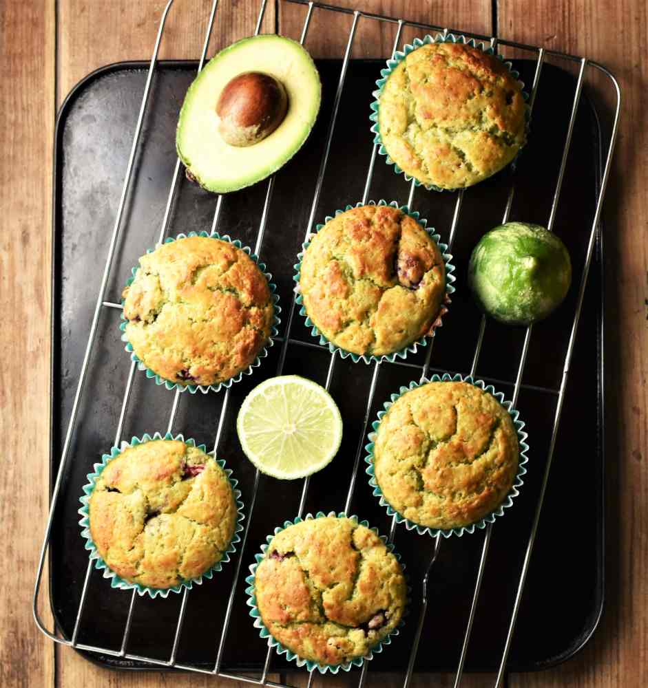 Avocado raspberry muffins with limes and halved avocado on top of cooling rack.