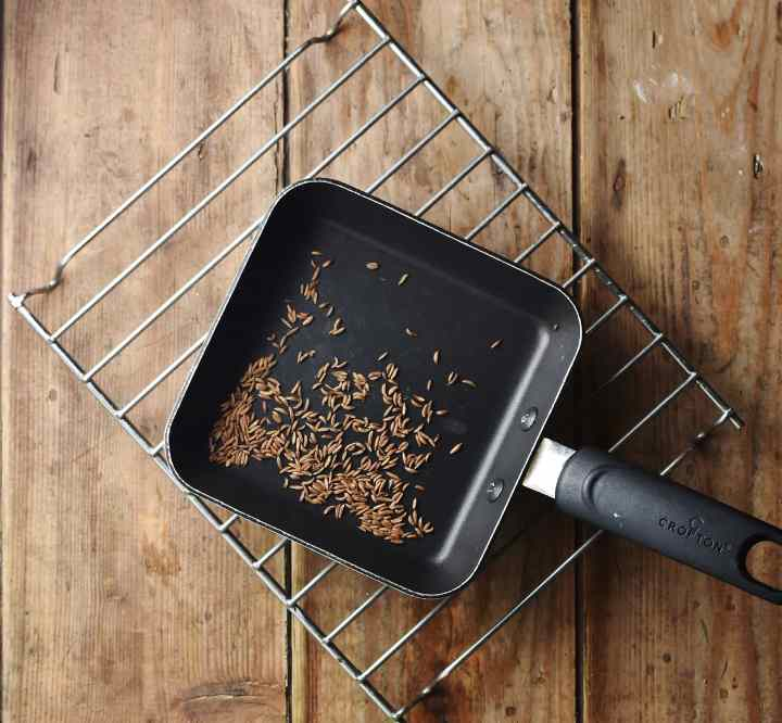 Caraway seeds in small square pan on top of rack.