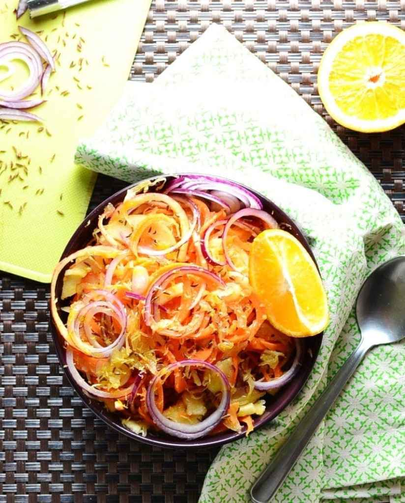 Top down view of Polish sauerkraut salad in purple bowl with orange, green cloth and partial view of yellow board.