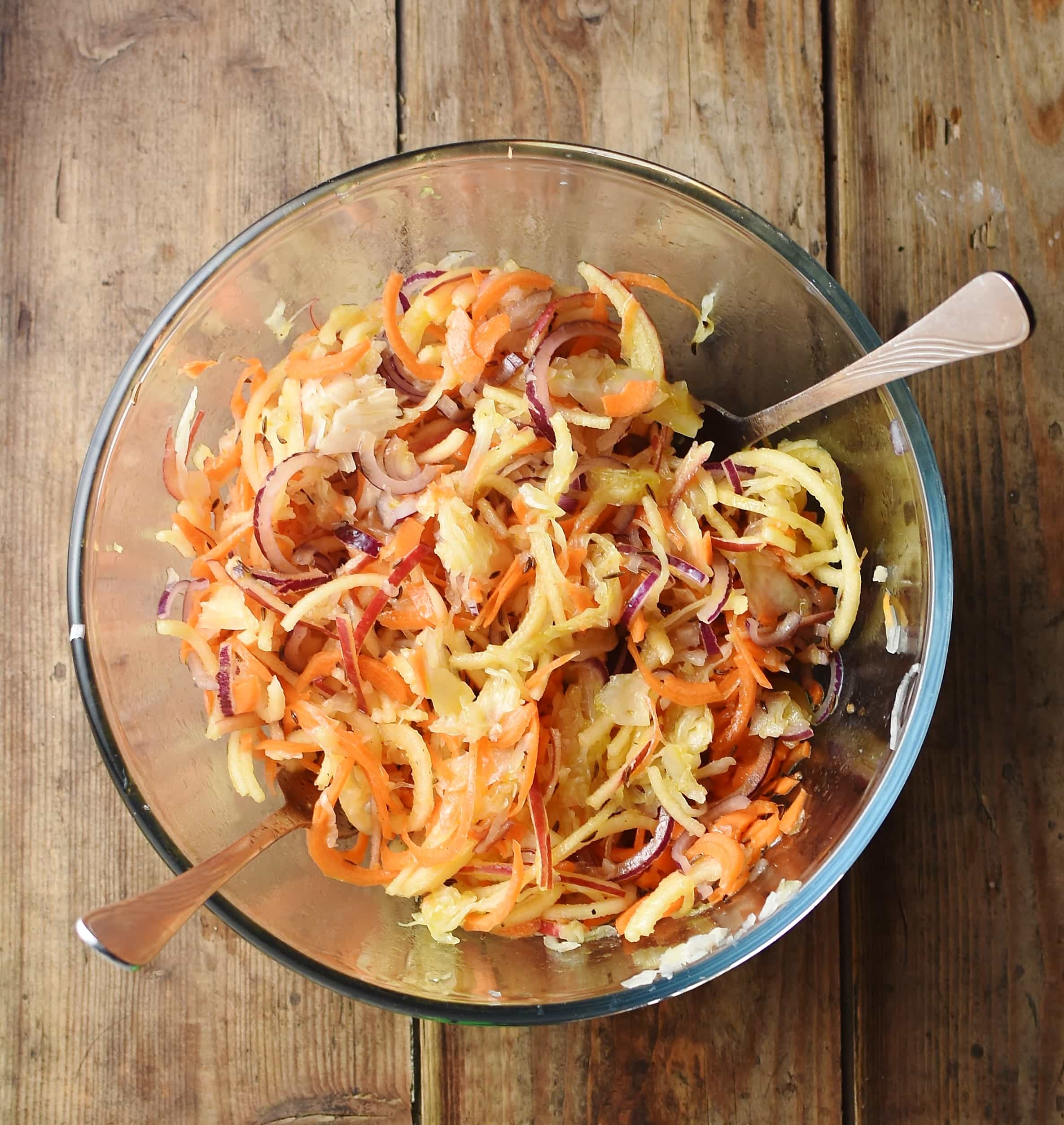 Sauerkraut, apple and carrot salad in mixing bowl with 2 forks.