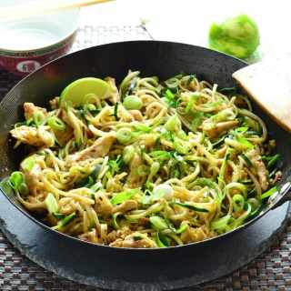 Chicken stir fry in wok with lime in background.