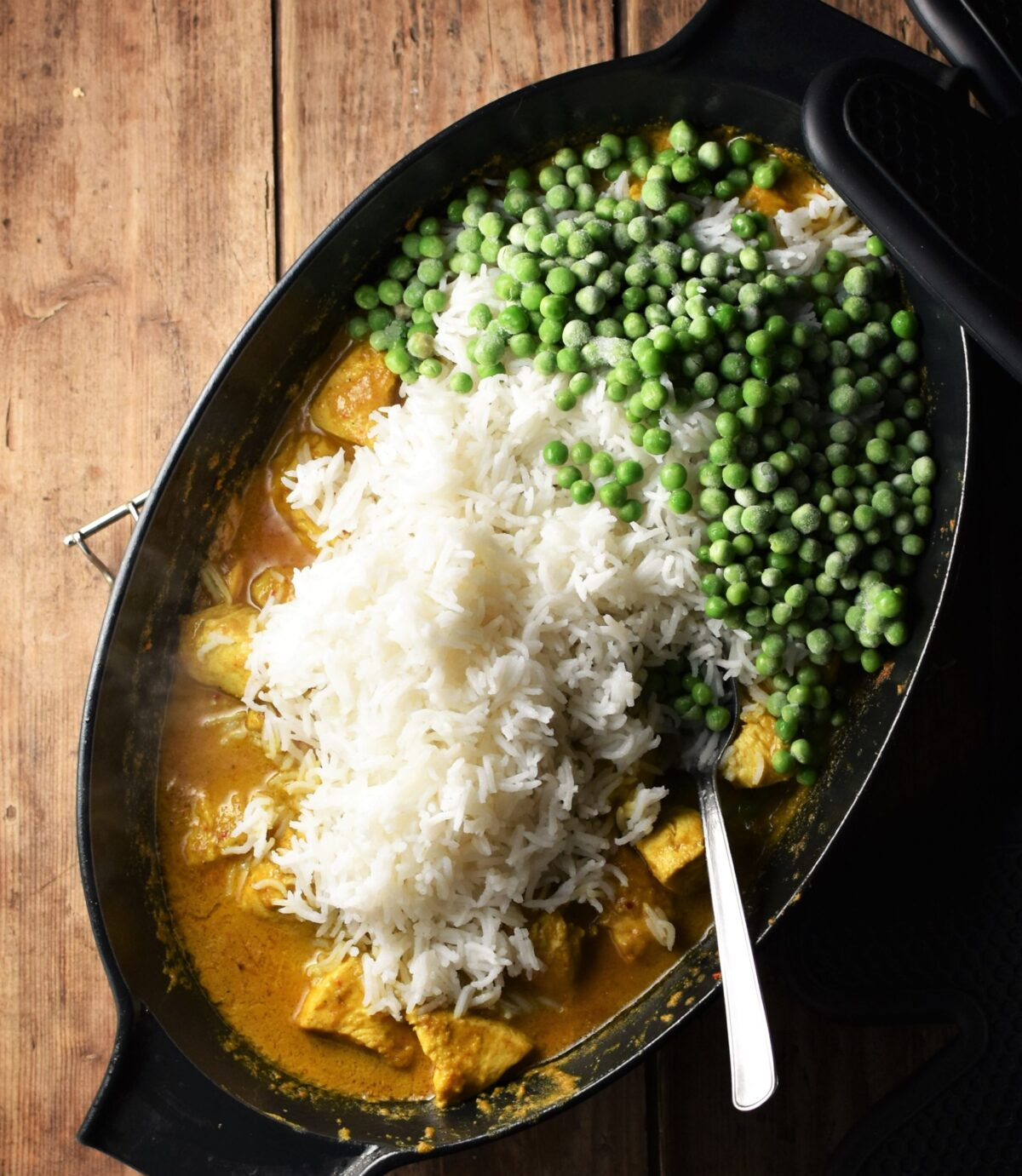 Cooked rice and peas on top of creamy chicken curry with spoon in large black oval pan.