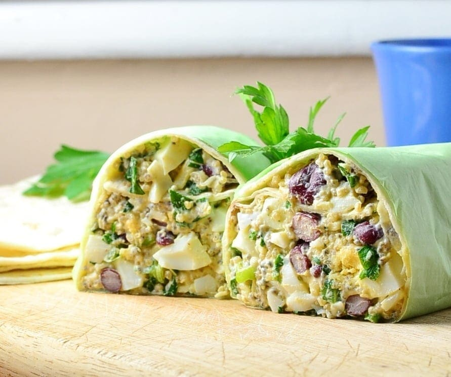 Close-up view of halved egg salad wrap on top of wooden board with parsley leaves and blue cup in background.