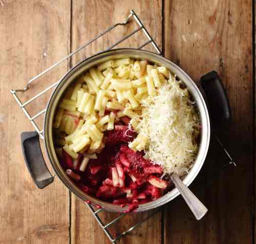 Macaroni, beet sauce and grated cheese in pot with spoon.