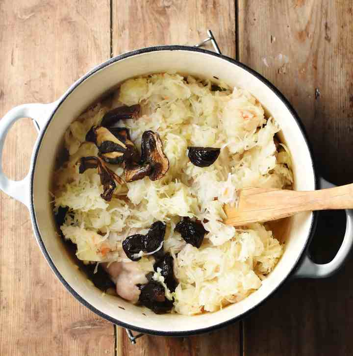 Sauerkraut, prunes and dried mushrooms in large white pot with wooden spoon.