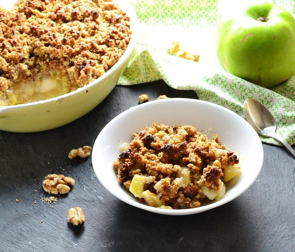 Apple crumble in white bowl, yellow dish with crumble and green cloth with green apple and spoon on top in background.