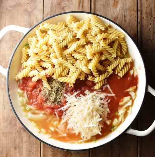 Fussili pasta, tomatoes, fennel and grated cheese in large white shallow dish.