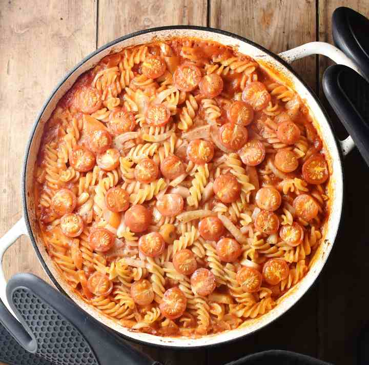 Baked tomato fennel pasta in large white casserole dish with black rubber gloves around handles.