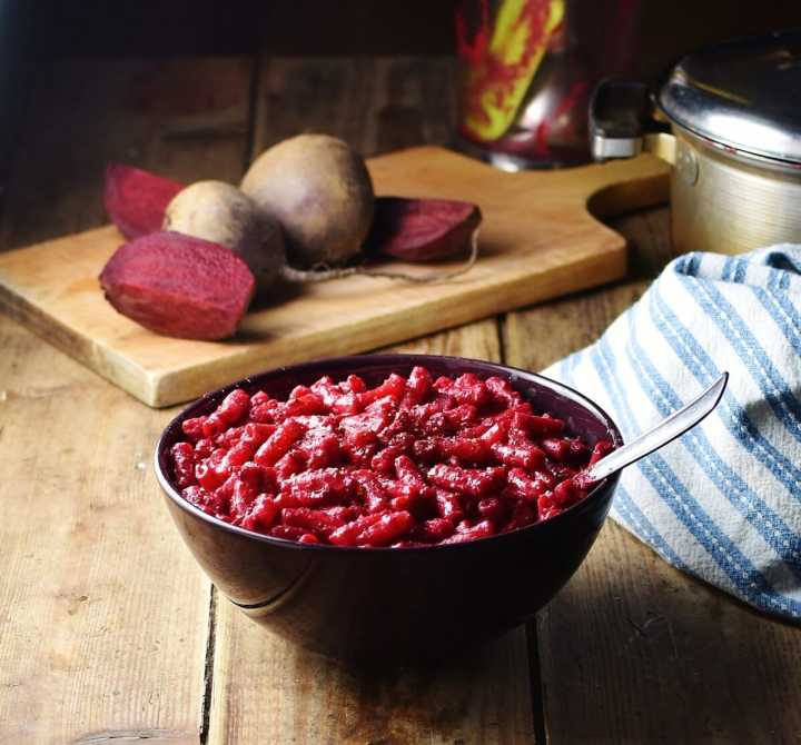 Beetroot macaroni in purple bowl with spoon, raw beets on wooden board and stripy blue cloth in background.