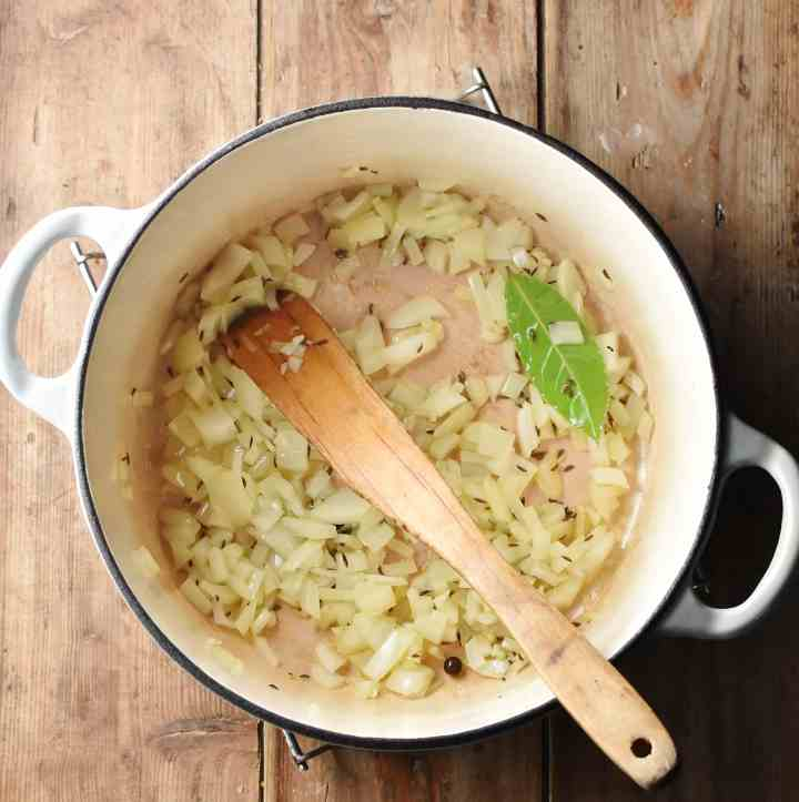 Chopped onion and spices in large white pot with wooden spatula.
